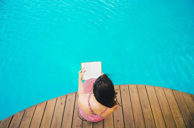 girl sitting reading book by the pool