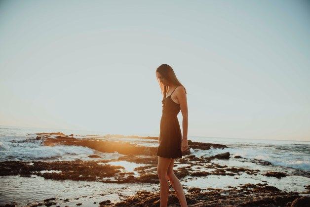 girl walking on beach smiling during sunset